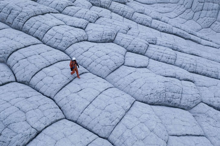 Kyle Hague walk across a moon-like mountain in the American Southwest