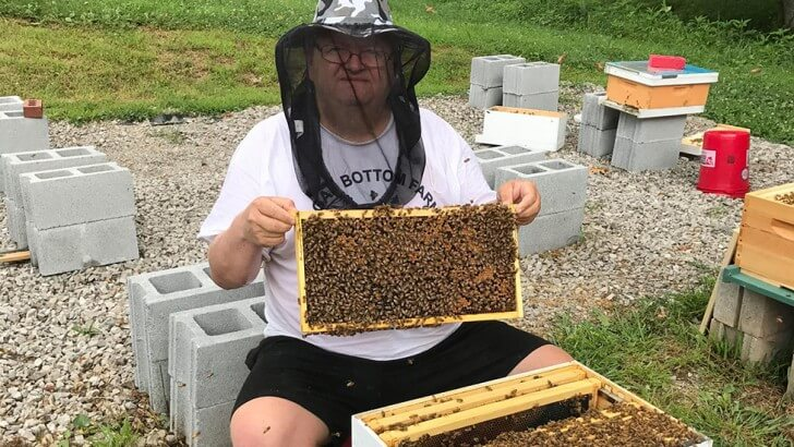 Eric Grandon holding a frame from his beehive