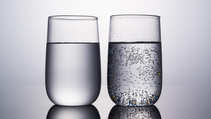 Two glasses of water, one with bubbles in it