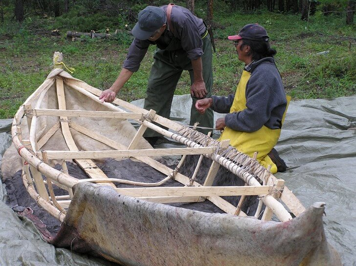 Angus Macdonald and Charlie Boya tie moose hide onto a boat frame