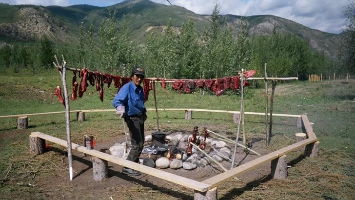 Charlie Boya drying moose meat at the Kaska Dena Youth Camp
