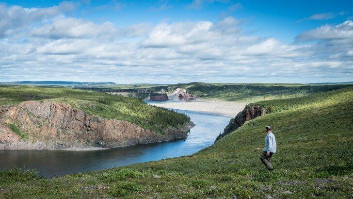 man walking by a river