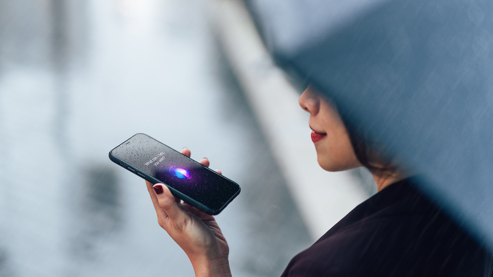 Woman using voice assistant on smartphone in the rain