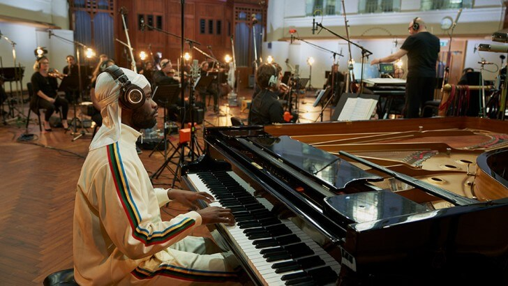 A pianist sits at the piano in a studio with an orchestra in the background