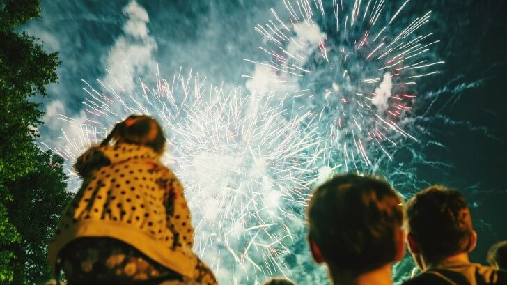 A fireworks display lights up the sky in front of a man and two children