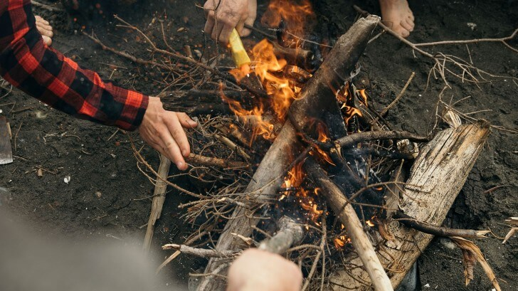 Three people try to keep a fire burning