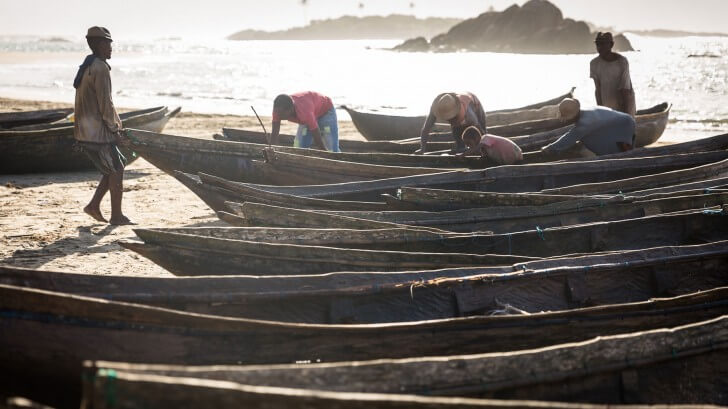 Fishermen pull pirogues up the beach at sunrise in Madagascar