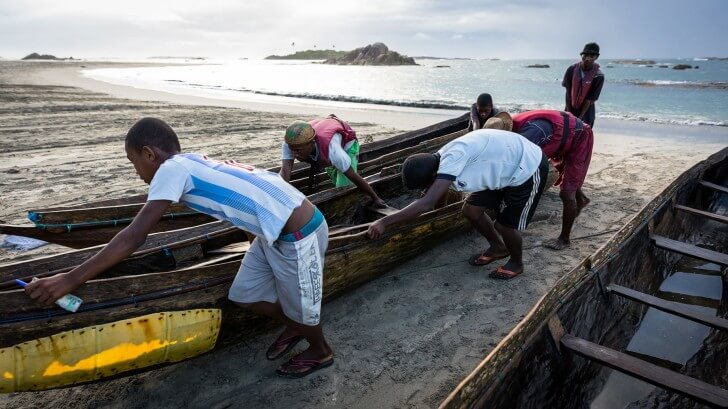Fishermen hauling in rickety wooden boats with plastic sheet repairs