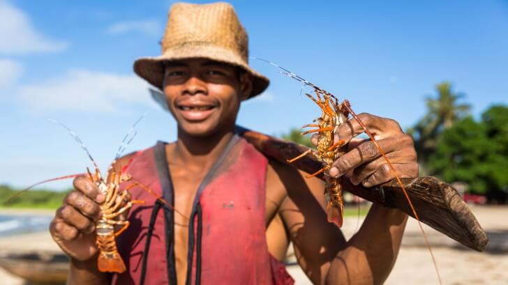 A fisherman called Merlin shows off two small lobsters