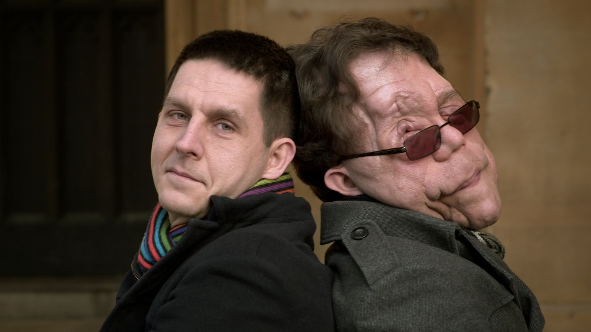 Actor Adam Pearson stands back to back with his brother Neil