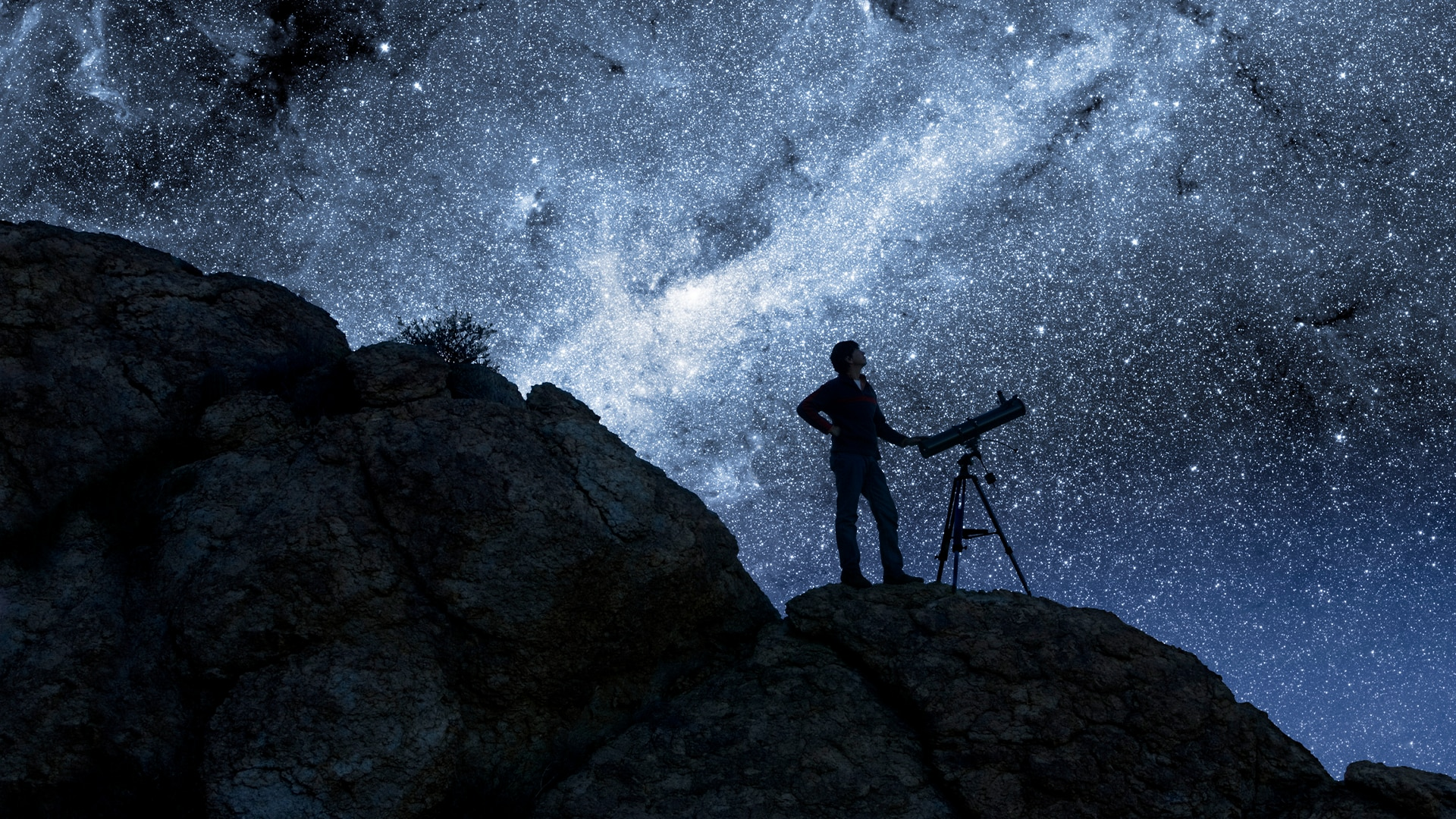 Person with telescope looking up to star filled night sky
